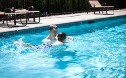 Niño pequeño de enseñanza del padre joven a nadar Imagenes de archivo