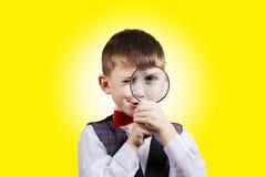 Niño pequeño de exploración curioso con la lupa foto de archivo