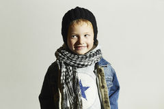 Niño pequeño de moda en bufanda y vaqueros Estilo del invierno Niños de la moda Niño divertido Sonrisa feliz Fotos de archivo libres de regalías