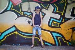 Niño pequeño de moda en gafas de sol y casquillo Fotografía de archivo