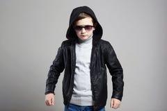Niño pequeño de moda en sudadera con capucha y gafas de sol fotos de archivo libres de regalías
