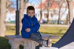 Niño pequeño de moda que presenta en el parque Foto de archivo