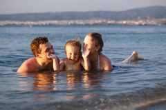 Niño pequeño de risa con sus padres en el mar foto de archivo libre de regalías