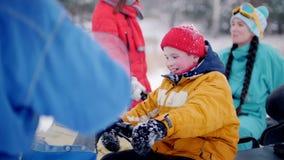 Niño pequeño del bosque A del invierno que se sienta en la moto de nieve y las torsiones la manija del gas almacen de video