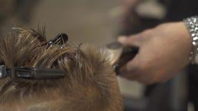 Niño pequeño del corte del peluquero de los niños con la maquinilla de afeitar eléctrica en salón de la peluquería Haidresser que almacen de metraje de vídeo