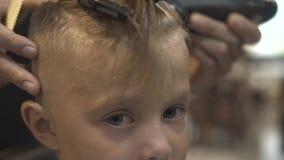 Niño pequeño del retrato mientras que corta con la maquinilla de afeitar eléctrica en cierre de la peluquería de caballeros para  almacen de video
