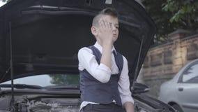 Niño pequeño del trastorno en un traje de negocios que se sienta al lado de la capilla abierta de un coche quebrado Niño como adu almacen de metraje de vídeo