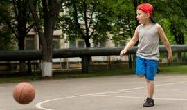 Niño pequeño deportivo que juega a baloncesto Imagen de archivo