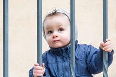 Niño pequeño detrás de barras imagen de archivo