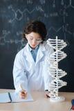 Niño pequeño diligente que hace notas en el laboratorio Fotografía de archivo