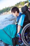 Niño pequeño discapacitado en silla de ruedas abajo por el agua en la playa Imagenes de archivo