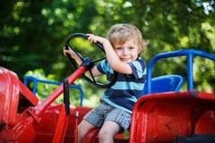 Niño pequeño divertido de tres años que juegan en el tractor Fotos de archivo libres de regalías