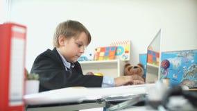 Niño pequeño divertido en traje de negocios y el sentarse en la tabla que mecanografían en el ordenador portátil almacen de metraje de vídeo