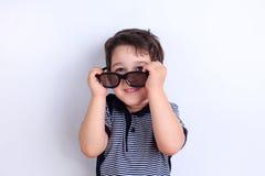 Niño pequeño divertido lindo con las gafas de sol, lanzamiento del estudio en blanco CH imagen de archivo