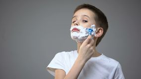 Niño pequeño divertido que afeita, fingiendo ser comportamiento adulto, de copiado de los padres almacen de video