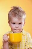 Niño pequeño divertido que bebe de la taza amarilla grande Foto de archivo libre de regalías
