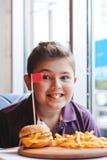Niño pequeño divertido que come una hamburguesa en un café, concepto de la comida Fotografía de archivo