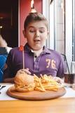 Niño pequeño divertido que come una hamburguesa en un café, concepto de la comida Fotos de archivo