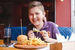 Niño pequeño divertido que come una hamburguesa en un café, concepto de la comida Fotografía de archivo libre de regalías