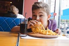 Niño pequeño divertido que come una hamburguesa en un café, concepto de la comida Imagenes de archivo