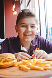 Niño pequeño divertido que come una hamburguesa en un café, concepto de la comida Foto de archivo