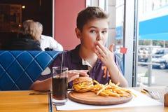 Niño pequeño divertido que come una hamburguesa en un café, concepto de la comida Foto de archivo libre de regalías