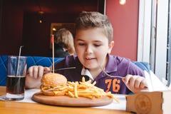 Niño pequeño divertido que come una hamburguesa en un café, concepto de la comida Fotos de archivo libres de regalías