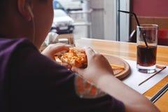 Niño pequeño divertido que come una hamburguesa en un café, concepto de la comida Imagen de archivo libre de regalías