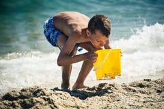 Niño pequeño divertido que juega en la playa con el cubo del juguete Fotografía de archivo