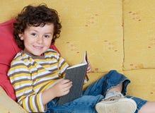 Niño pequeño divertido que lee un libro en el sofá fotos de archivo