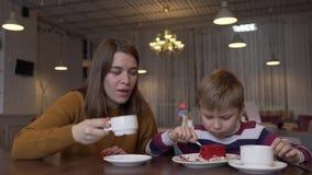 Niño pequeño divertido y té joven hermoso de la bebida de la madre y comer la torta almacen de metraje de vídeo