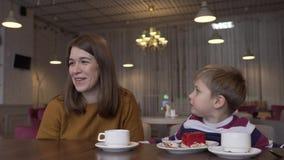 Niño pequeño divertido y té joven hermoso de la bebida de la madre y comer la torta metrajes