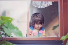 Niño pequeño dulce, jugando con el aeroplano temprano por la mañana Foto de archivo libre de regalías
