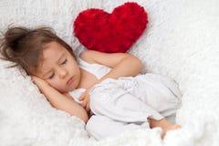 Niño pequeño, durmiendo en una silla grande Fotos de archivo libres de regalías