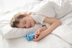 Niño pequeño durmiente sonriente feliz con el despertador cerca de su cabeza Fotos de archivo libres de regalías