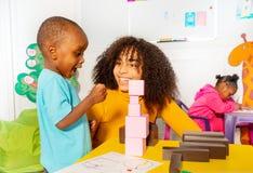 Niño pequeño emocionado en cuarto de niños sobre torre del bloque fotografía de archivo
