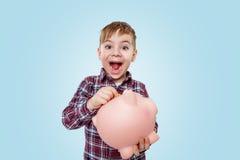 Niño pequeño emocionado que sostiene la caja de dinero y que mira la cámara Foto de archivo