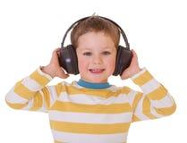 Niño pequeño en auriculares Fotos de archivo