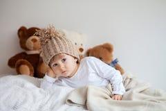 Niño pequeño en cama con los osos de peluche alrededor Foto de archivo libre de regalías