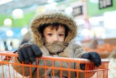 Niño pequeño en carro de compras Fotos de archivo libres de regalías