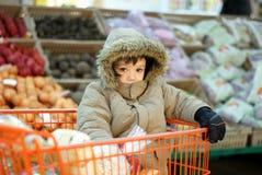 Niño pequeño en carro de compras Foto de archivo