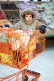 Niño pequeño en carro de compras Fotografía de archivo libre de regalías