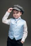 Niño pequeño en casquillo y chaleco azul Fotografía de archivo