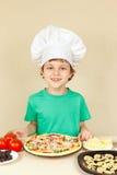 Niño pequeño en cocinero del sombrero con la pizza hecha en casa cocinada Imagen de archivo