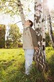 Niño pequeño en el árbol de abedul en parque Imagenes de archivo