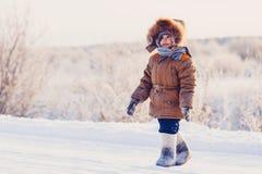 Niño pequeño en el camino nevoso del invierno Imágenes de archivo libres de regalías