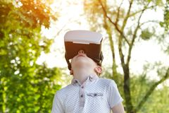Niño pequeño en el casco de la realidad virtual que mira para arriba Fotografía de archivo