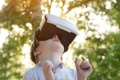 Niño pequeño en el casco de la realidad virtual que mira para arriba Fotos de archivo