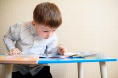 Niño pequeño en el escritorio que lee un libro Fotografía de archivo libre de regalías