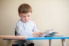 Niño pequeño en el escritorio que lee un libro Fotografía de archivo